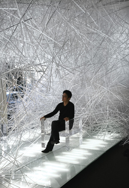 Tokujin Yoshioka sitting on the new Invisible Project by Kartell, Milan 2010
