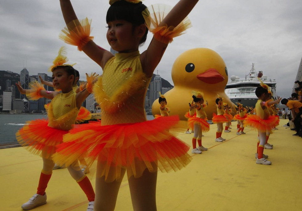 Dancers perform during a welcoming ceremony of a giant Rubber Duck created by artist Florentijn Hofman in Hong Kong, 2013. (16.5-meters)